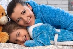 Gelukkige moeder en dochter in blauwe badstof robes royalty-vrije stock afbeeldingen