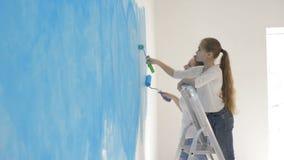 Gelukkige moeder en dochter die een muur met een blauwe rol schilderen stock videobeelden