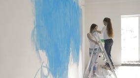 Gelukkige moeder en dochter die een muur met een blauwe rol schilderen stock video