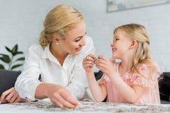 gelukkige moeder en dochter die elkaar glimlachen terwijl het spelen met raadselstukken royalty-vrije stock afbeelding