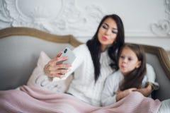 Gelukkige moeder en dochter die grappige Kerstmis thuis nemen selfies royalty-vrije stock afbeeldingen