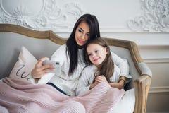 Gelukkige moeder en dochter die grappige Kerstmis thuis nemen selfies stock foto