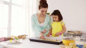Gelukkige moeder en dochter die koekjes thuis maken stock video