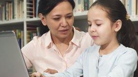 Gelukkige moeder en dochter die laptop met behulp van terwijl het bestuderen stock footage