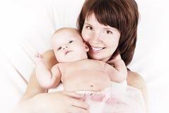 Gelukkige moeder en dochter die op het bed liggen stock afbeeldingen