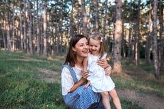 Gelukkige moeder en dochter die samen in openlucht zingen stock foto