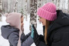 Gelukkige moeder en dochter in een de winterbos Royalty-vrije Stock Afbeeldingen