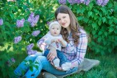 Gelukkige moeder en dochter met groene appelen in de tuin van bloeiende seringen royalty-vrije stock foto