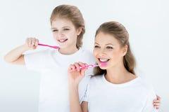 Gelukkige moeder en dochter schoonmakende tanden met tandenborstels stock afbeeldingen