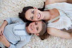 Gelukkige moeder en haar meisje die op de vloer liggen Stock Fotografie