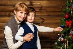 Gelukkige moeder en haar weinig jongen die Kerstmisboom verfraaien Stock Fotografie