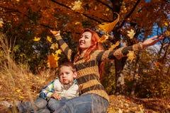 Gelukkige moeder en haar weinig zoon die en pret in de herfstbos lopen hebben Stock Afbeelding