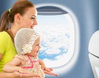 Gelukkige moeder en jong geitjezitting dichtbij vliegtuigvenster Stock Afbeelding