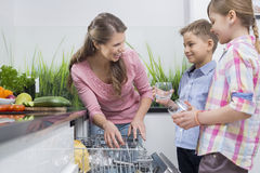 Gelukkige moeder en kinderen die glazen plaatsen in afwasmachine Stock Afbeeldingen