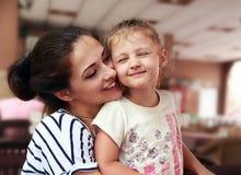 Gelukkige moeder en leuk het genieten van meisje geknuffel met liefde binnen stock foto