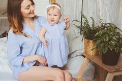 Gelukkige moeder en 9 maand oude baby in de aanpassing van pyjama's die in slaapkamer in de ochtend spelen Stock Foto's