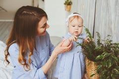 Gelukkige moeder en 9 maand oude baby in de aanpassing van pyjama's die in slaapkamer in de ochtend spelen Royalty-vrije Stock Afbeeldingen
