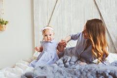 Gelukkige moeder en 9 maand oude baby in de aanpassing van pyjama's die in slaapkamer in de ochtend spelen Stock Foto