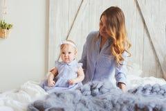Gelukkige moeder en 9 maand oude baby in de aanpassing van pyjama's die in slaapkamer in de ochtend spelen Stock Afbeeldingen