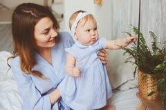 Gelukkige moeder en 9 maand oude baby in de aanpassing van pyjama's die in slaapkamer in de ochtend spelen Stock Fotografie