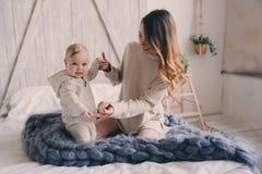 Gelukkige moeder en 8 maand oude baby die en thuis in slaapkamer in de ochtend spelen ontspannen Royalty-vrije Stock Foto