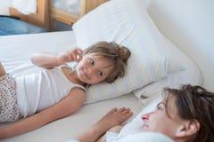 Gelukkige moeder en meisjesdochterontwaken op bed bij ochtend samen Gelukkige ontspannen ouders die van het leven met hun geniete Royalty-vrije Stock Afbeelding