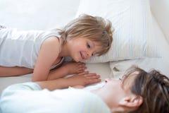 Gelukkige moeder en meisjesdochterontwaken op bed bij ochtend samen Gelukkige ontspannen ouders die van het leven met hun geniete Stock Fotografie