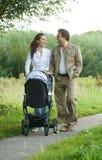 Gelukkige moeder en vader duwende babykinderwagen in openlucht Royalty-vrije Stock Foto's