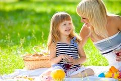 Gelukkige moeder en weinig dochter bij een picknick Stock Foto's