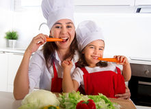 Gelukkige moeder en weinig dochter die in schort en kokhoed wortelen eten die samen pret thuis keuken hebben Stock Foto