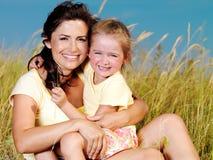 Gelukkige moeder en weinig dochter op aard royalty-vrije stock foto's
