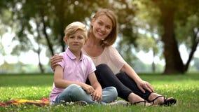 Gelukkige moeder en zoon die camera, advertentie bekijken van sociale steun voor enige moeders royalty-vrije stock afbeelding