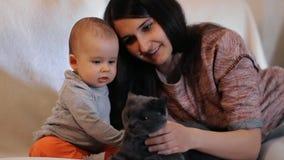 Gelukkige moeder en zoons glimlachende en petting kat stock footage