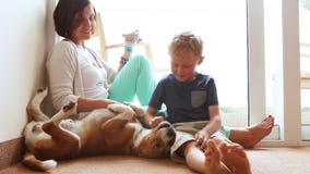 Gelukkige moeder en zoonsfamilie op de huisvloer met vriendschappelijke brakhond