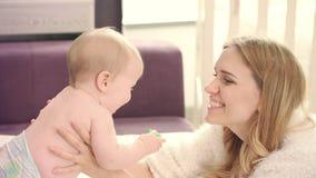Gelukkige moeder kussende baby Jonge moeder knuffelende baby stock videobeelden