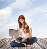 Gelukkige moeder met aanbiddelijke meisje en laptop Royalty-vrije Stock Afbeeldingen