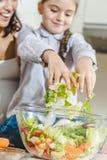gelukkige moeder met dochter die plantaardige salade maken royalty-vrije stock afbeelding