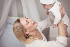 Gelukkige moeder met haar baby Stock Afbeelding