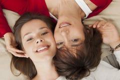 Gelukkige Moeder met haar dochter die op het bed rusten Stock Fotografie