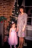 Gelukkige moeder met haar dochter door de open haard dichtbij Kerstboom Stock Foto