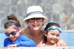 Gelukkige moeder met haar jonge geitjes in de pool stock afbeeldingen