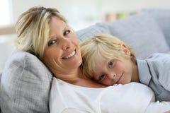 Gelukkige moeder met haar zoon die op bank rusten royalty-vrije stock foto's