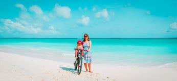 Gelukkige moeder met leuk weinig fiets van het babymeisje bij strand stock afbeelding