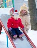 Gelukkige moeder met peuter het spelen op dia Royalty-vrije Stock Foto