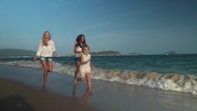Gelukkige moeder met twee dochters die langs het strand van Overzees het Zuid- van China, Yalong-video van de de voorraadlengte v stock videobeelden