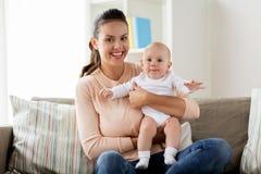 Gelukkige moeder met weinig babyjongen thuis stock foto