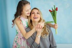 Gelukkige moeder`s dag De kinddochter wenst mamma's geluk en geeft haar een prentbriefkaar en bloeit tulpen royalty-vrije stock afbeelding