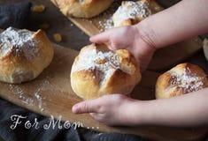 Gelukkige moeder`s dag Het kind houdt een broodje, het ` s een gift voor mamma Stock Afbeelding