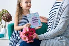 Gelukkige moeder`s dag Leuk meisje die de kaart van de mammagroet, heden en boeket van roze gerberamadeliefjes geven Moeder en do stock afbeelding