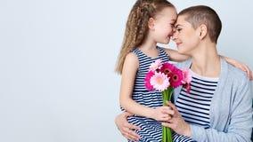 Gelukkige Moeder` s Dag, Vrouwen` s dag of Verjaardagsachtergrond Leuk meisje die mammaboeket van roze gerberamadeliefjes geven H royalty-vrije stock fotografie